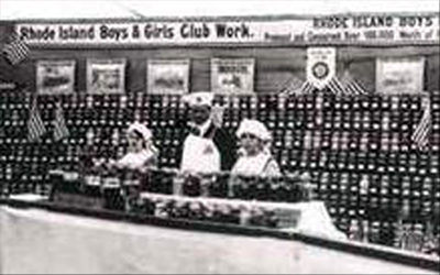 Rhode Island Club girls show their patriotism with this 1918 exhibit of canned produce they have grown and preserved. Notice the flags among the canned goods.